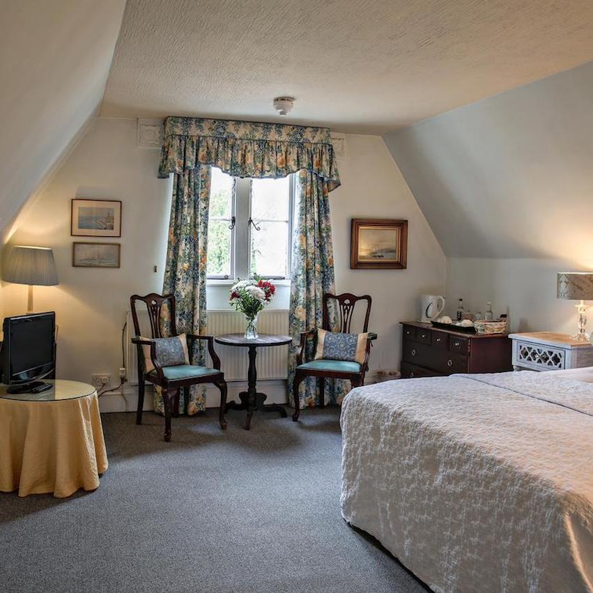 Double room with table and chairs at our beautiful B & B in Hampshire